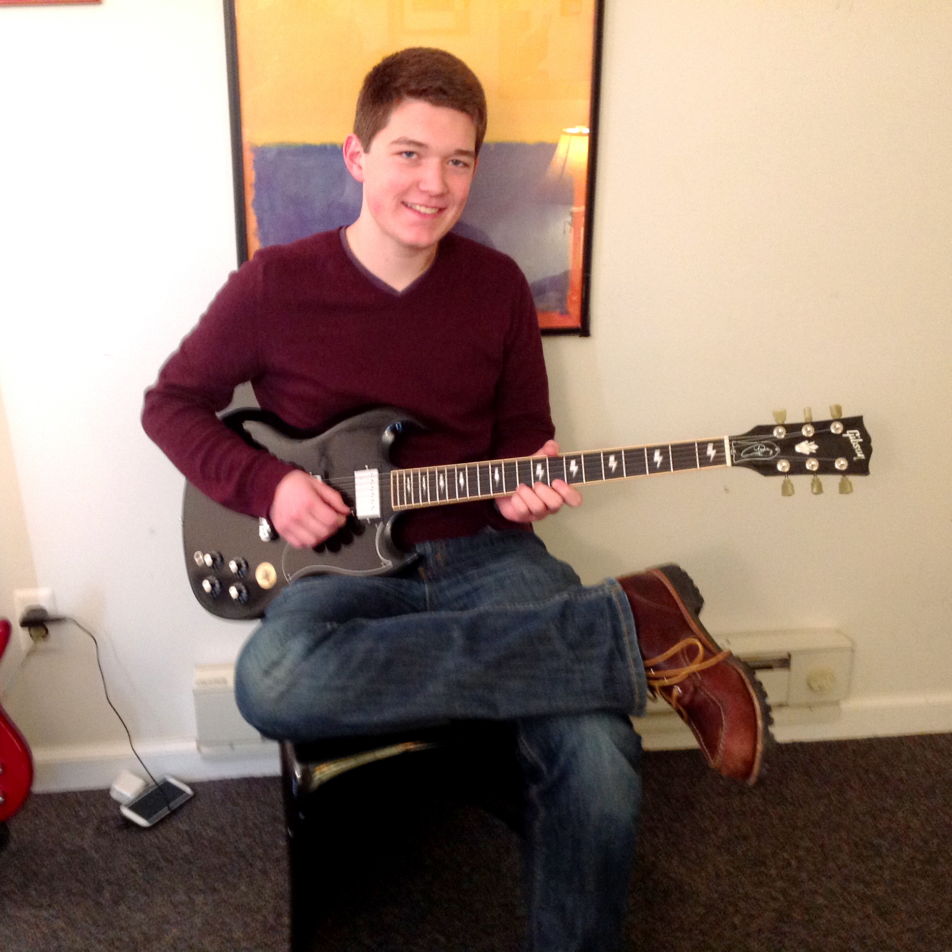 Young man playing a black Gibson SG